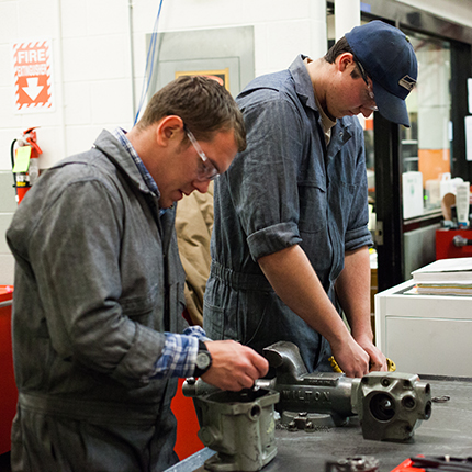 Auto students working on parts.