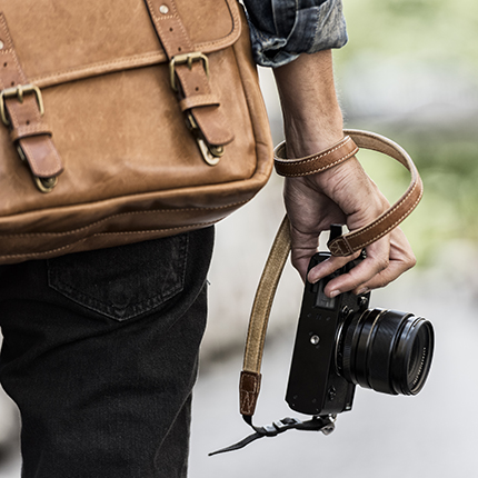 Close up of someones hand holding a camera and a bag.