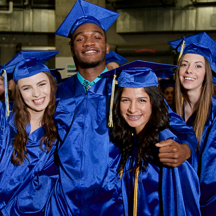 Four graduates in caps and gowns