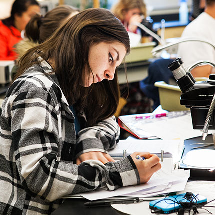 A female student dressed in a black and white plaid sweater writing on pieces of paper at a desk while students sit behind her in frame.