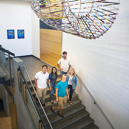 five students walking down the stairs under a sculpture in the Gateway Building