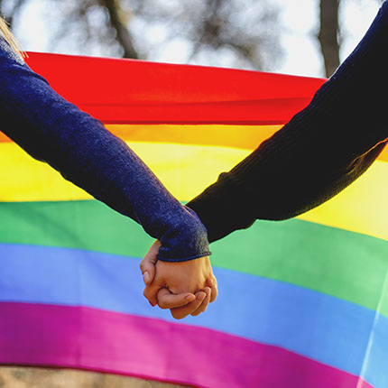 Holding hands in front of a pride flag