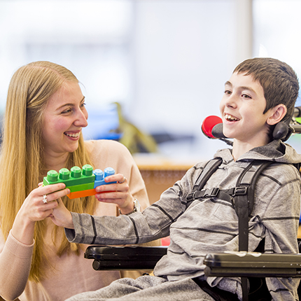 A teacher shows her student some legos