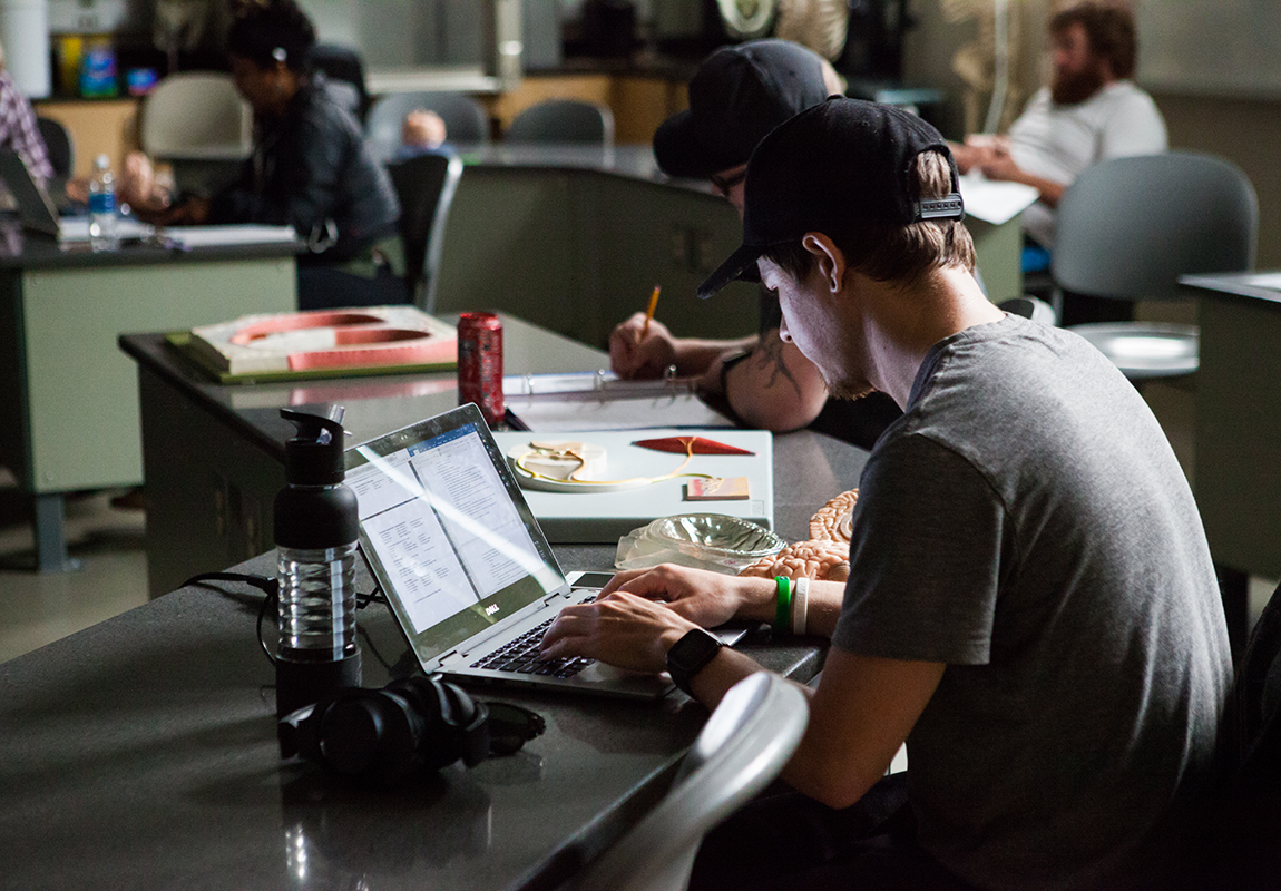 An SFCC student doing work on a laptop
