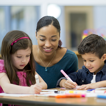 A teacher helps her young students