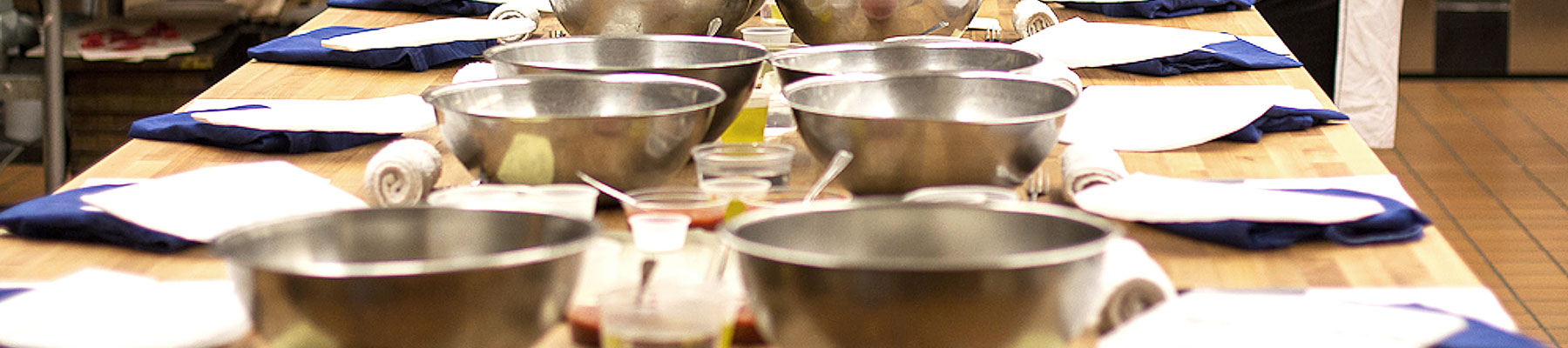 a table set with stainless steel mixing bowls, ready for class