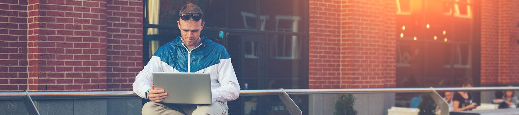 Male outside on laptop