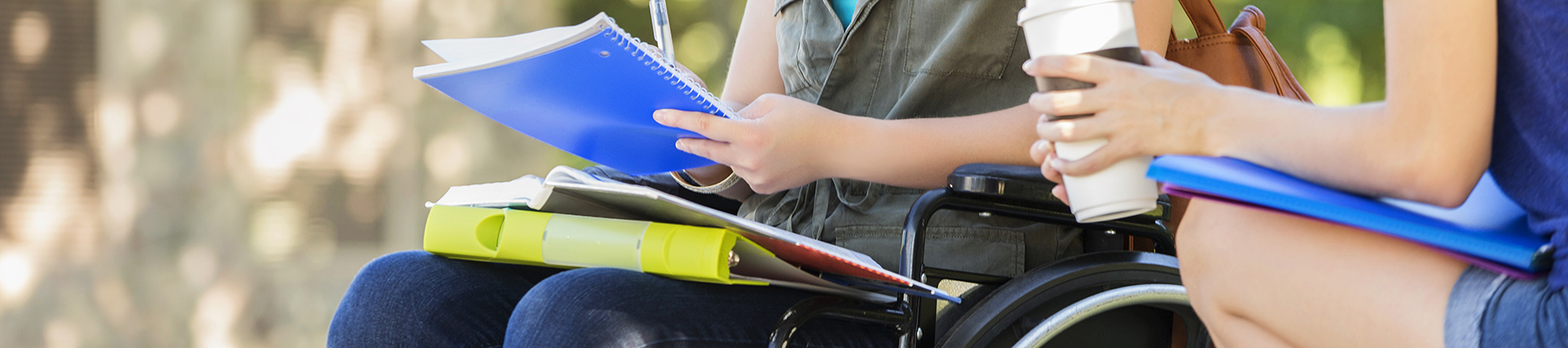 close up on two students talking to each other, one is in a wheel chair