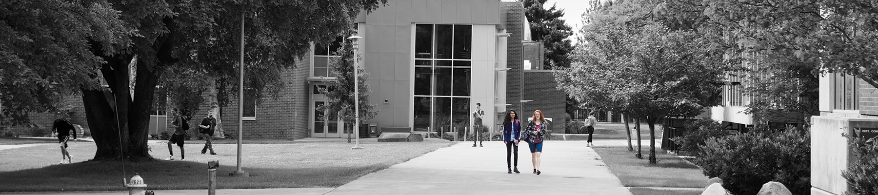 Two female students walking to class at SFCC's campus. Photo is in black and white while the students are in color.