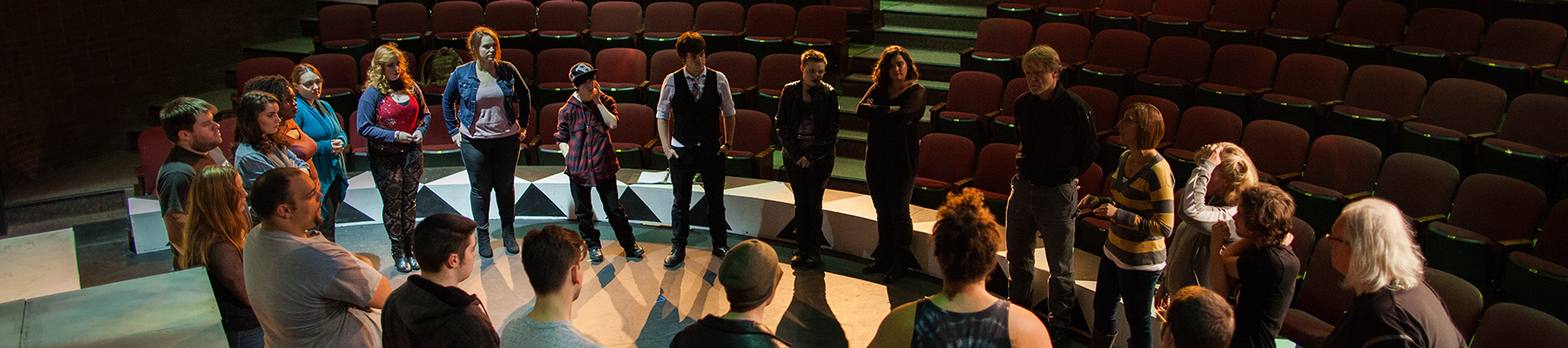 Students standing in circle on theater stage
