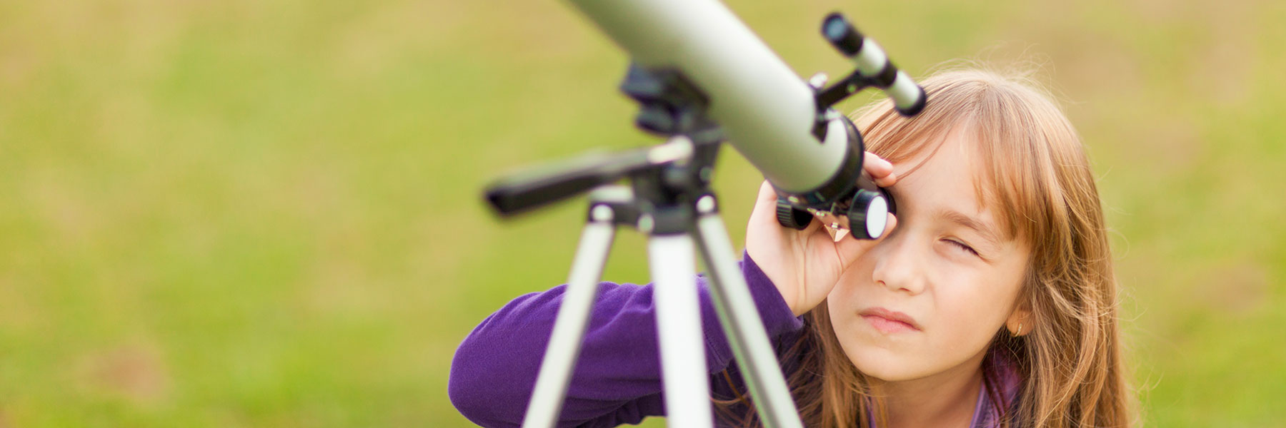young girl looking through telescope