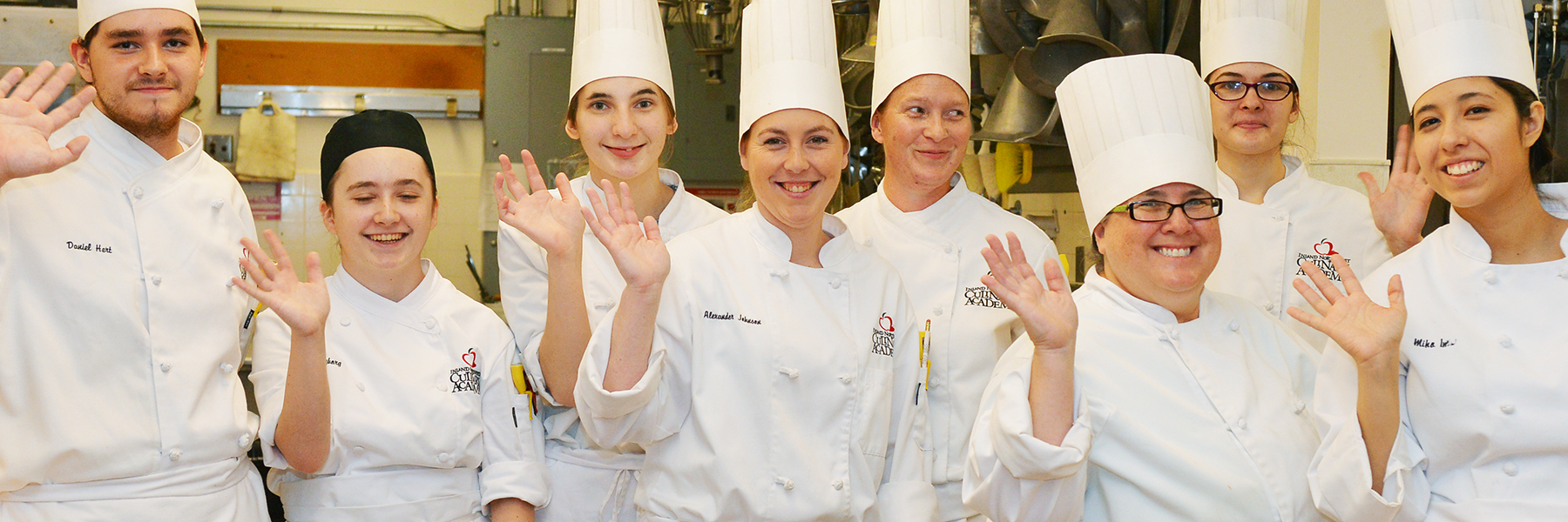 Group of pastry chef students waving at camera