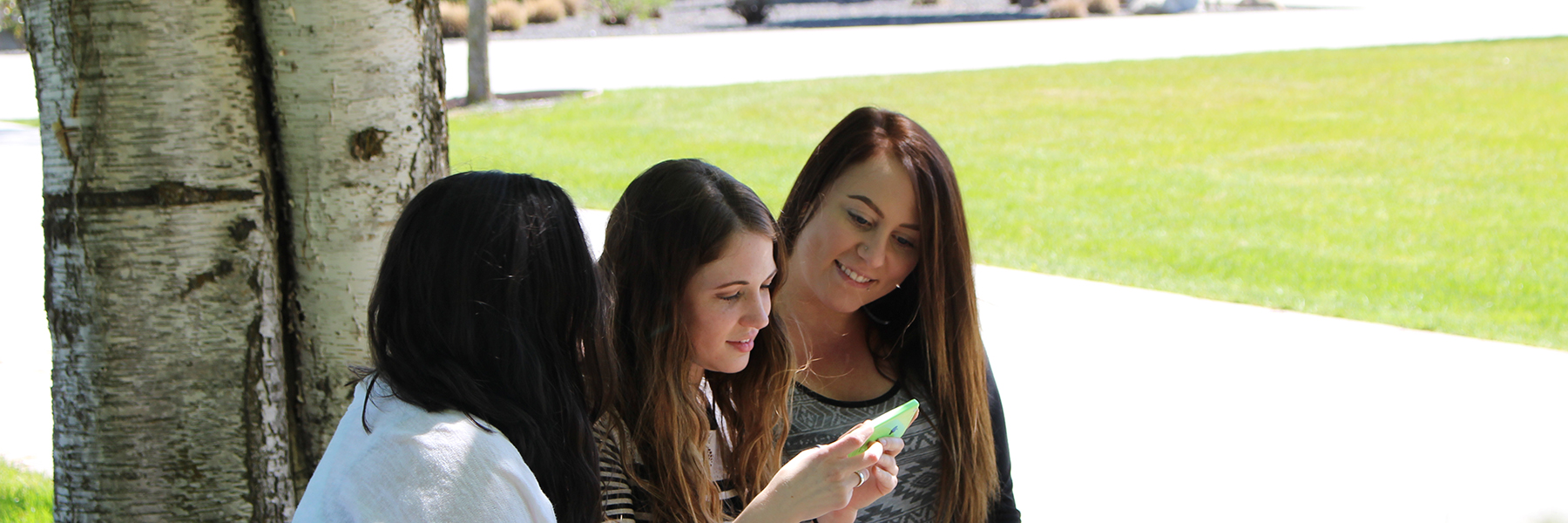 Three students sitting outside looking at a cell phone