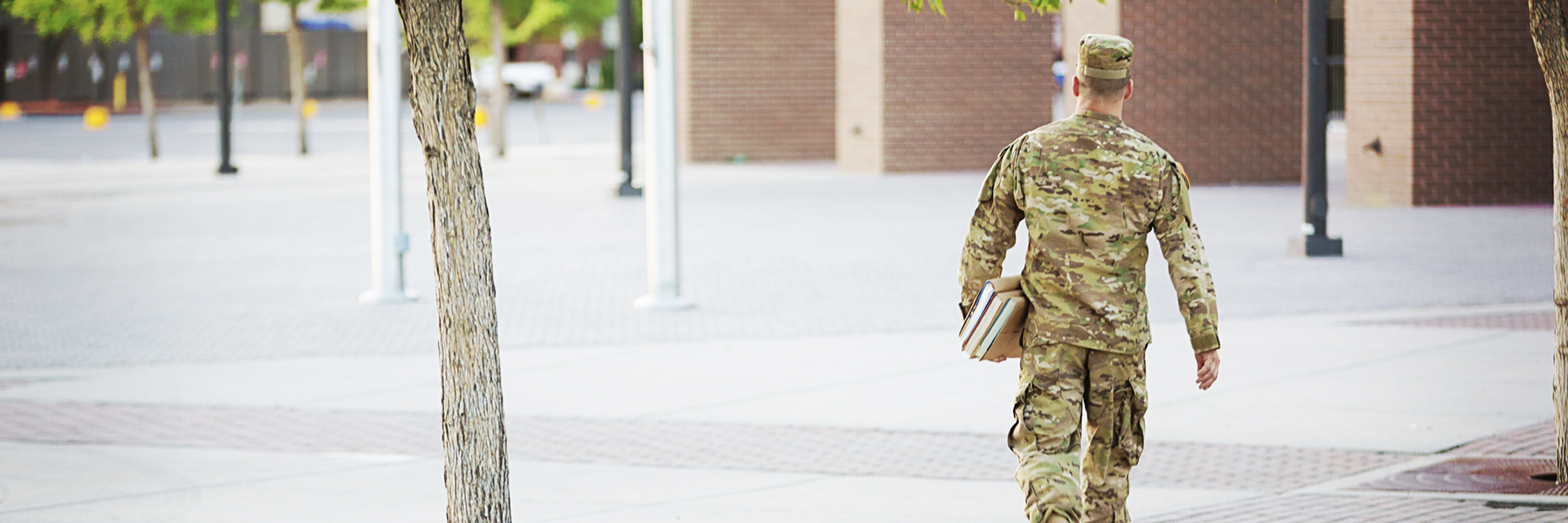 Man in uniform walking on campus with books under his arm