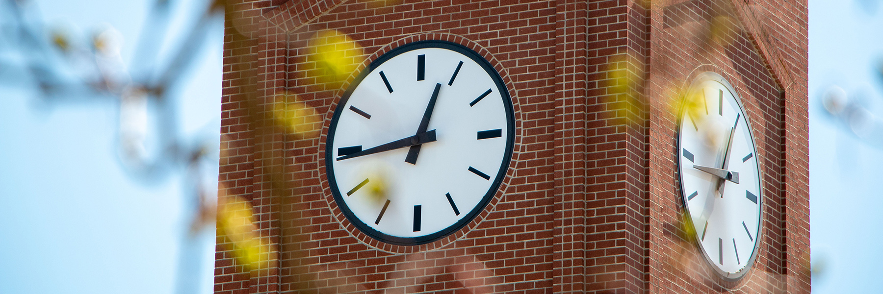 A picture of the SFCC clocktower, zoomed in so you can only see the watch faces and the brick. It's sunny out and the sky is blue behind the tower.