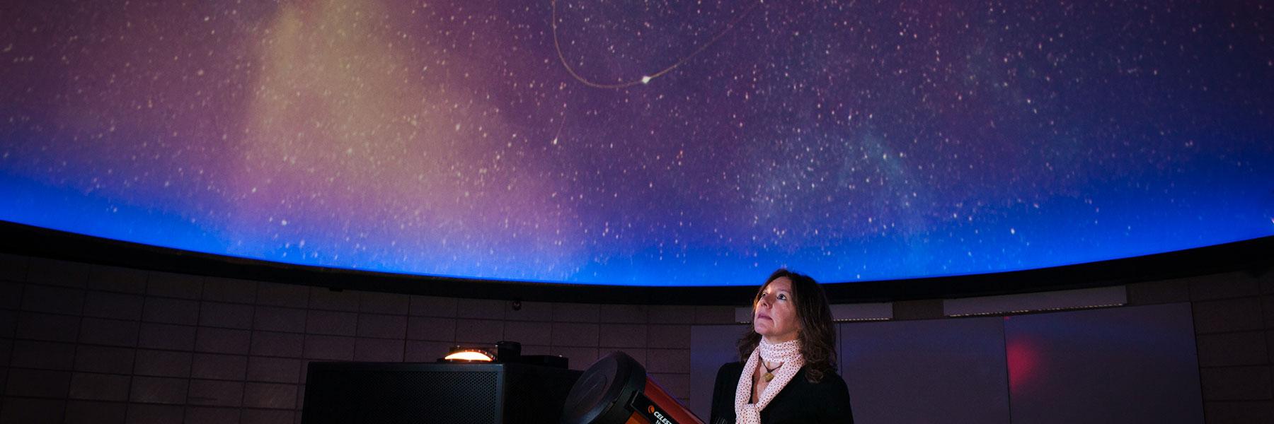 Instructor inside planetarium displaying night sky