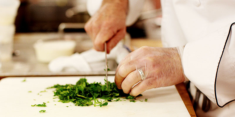 close up of hands chopping herbs