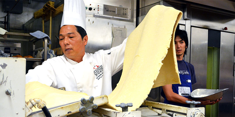 A chef running pasta dough through a pasta maker