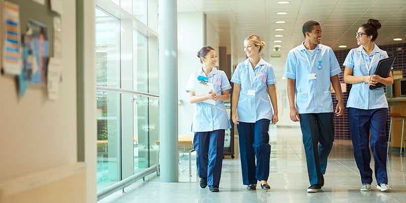 four healthcare workers in hallway