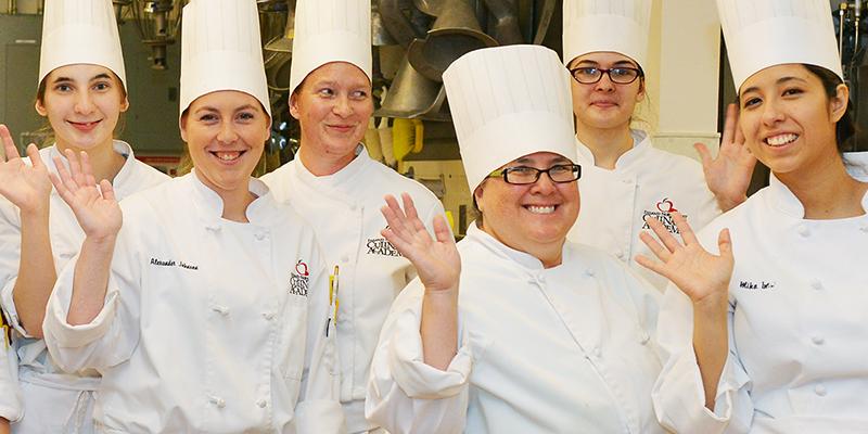 Group of pastry chef students waving at camera