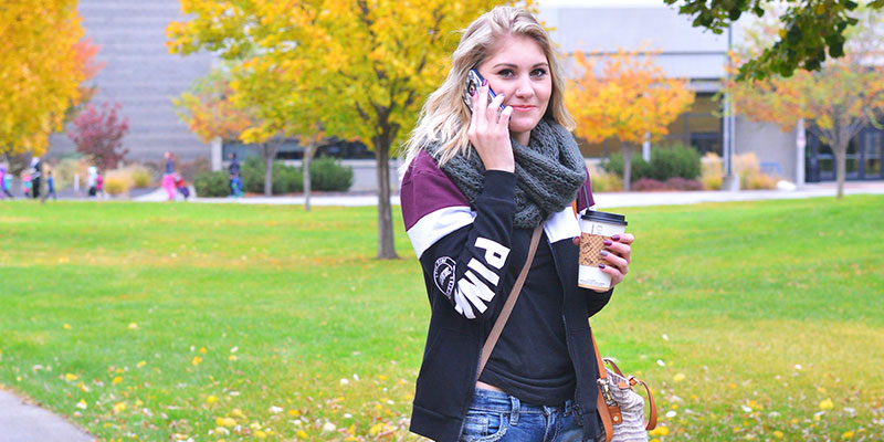 Girl walking with coffee in hand talking on her cell phone