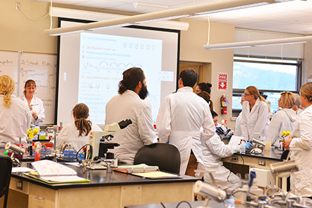 Students wearing labcoats in SCC science classroom.