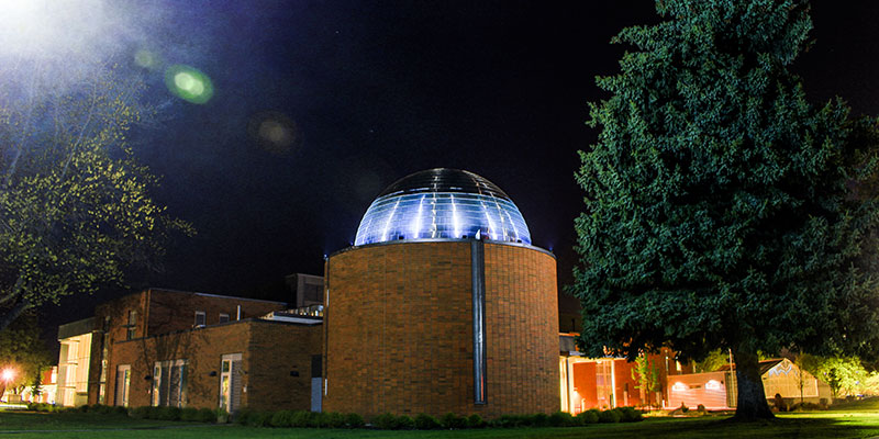 Outdoor view of the Science Building with the Planetarium in full view at night