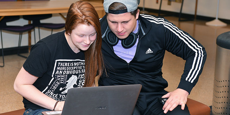 Students work on a laptop together