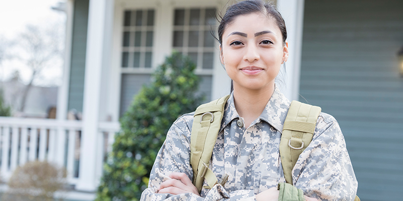 Young woman in miitary uniform standing in front of a house