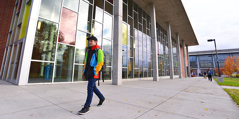 Student walking in front of the music building on the SFCC campus.