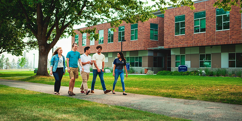 Five students walking through campus
