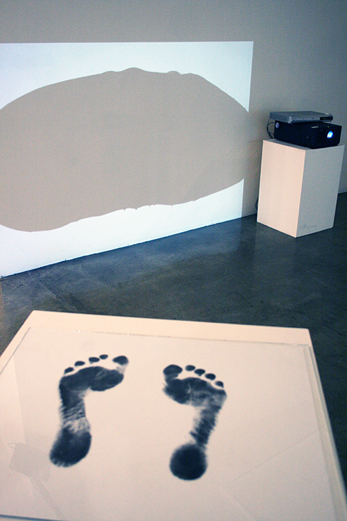 Mixed Media Traps installation view - two foot prints on a piece of paper