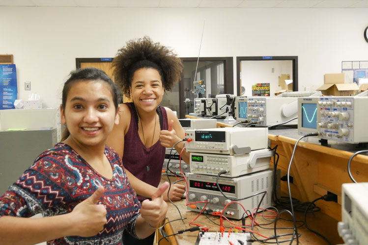 Two women working with electronics equipment.