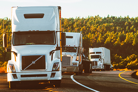 three trucks parked next to a road at sunrise