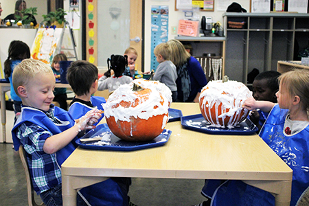 Children decorating pumkins with shaving cream