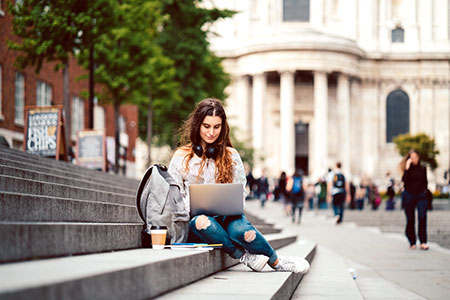 female student with laptop on steps