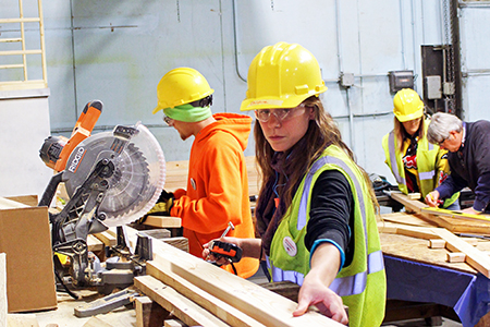 Female apprentice operating a table saw