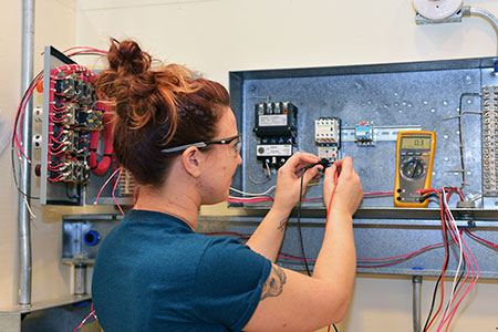 student measuring current with a multimeter