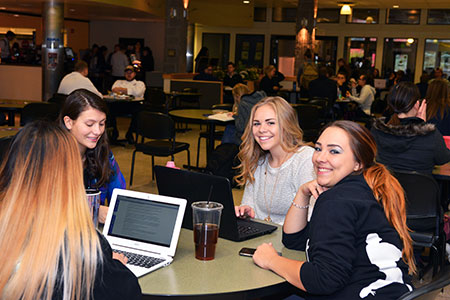 four students at table on laptop