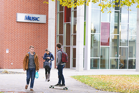 Students walking and infront of the Music building entrance