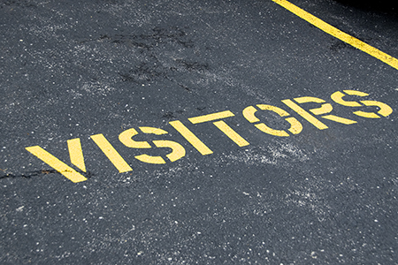 The word visitors painted on the asphalt of a parking space