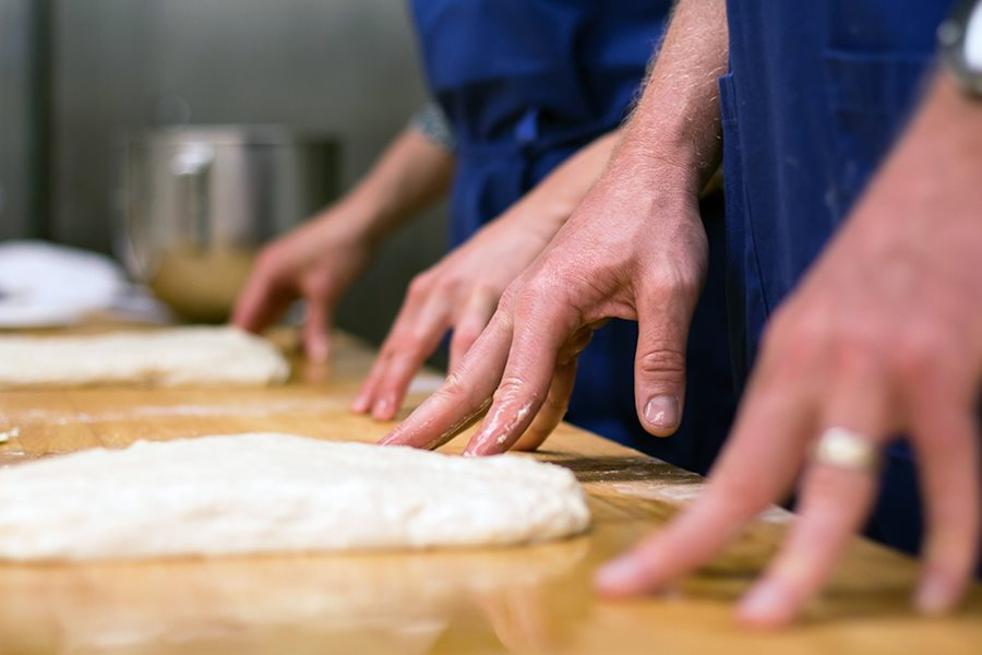Hands on pizza dough in teaching kitchen